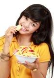 Adolescente sonriente que come un tazón de fuente de frutas cortadas Fotografía de archivo