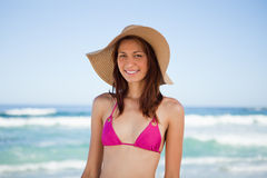 Adolescente sonriente que desgasta un sombrero mientras que se coloca Imagenes de archivo
