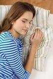 Adolescente sonriente que duerme en el sofá en casa Foto de archivo libre de regalías
