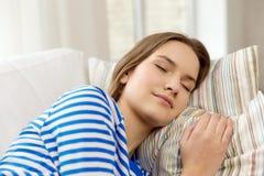 Adolescente sonriente que duerme en el sofá en casa Fotos de archivo libres de regalías