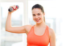 Adolescente sonriente que ejercita con pesa de gimnasia Foto de archivo