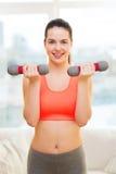 Adolescente sonriente que ejercita con pesas de gimnasia Imágenes de archivo libres de regalías