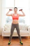 Adolescente sonriente que ejercita con pesas de gimnasia Fotos de archivo