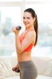 Adolescente sonriente que ejercita con pesas de gimnasia Foto de archivo libre de regalías