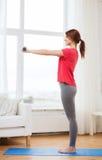 Adolescente sonriente que ejercita con pesas de gimnasia Imagen de archivo libre de regalías