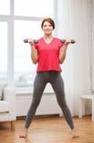 Adolescente sonriente que ejercita con pesas de gimnasia Imagen de archivo