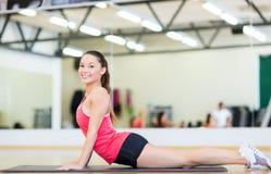 Adolescente sonriente que estira en la estera en el gimnasio Fotos de archivo libres de regalías