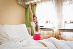 Adolescente sonriente que estira las manos después de wakening en la mañana Imagen de archivo libre de regalías