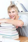 Adolescente sonriente que estudia muchos libros Foto de archivo