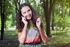 Adolescente sonriente que habla al aire libre móvil Imagen de archivo