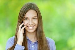 Adolescente sonriente que habla en el teléfono móvil Fotografía de archivo libre de regalías