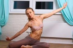 Adolescente sonriente que hace ejercicio en piso en casa Imagenes de archivo