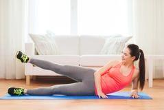 Adolescente sonriente que hace el ejercicio para las piernas Imagen de archivo
