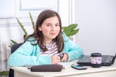 Adolescente sonriente que hace la preparación en casa Fotografía de archivo