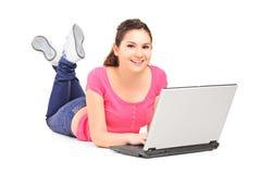 Adolescente sonriente que hace su preparación en una computadora portátil Imágenes de archivo libres de regalías