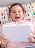 Adolescente sonriente que juega con la tableta en casa Imágenes de archivo libres de regalías