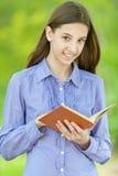 Adolescente sonriente que lee el libro anaranjado Fotos de archivo
