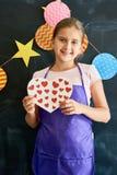 Adolescente sonriente que lleva a cabo el corazón Imagen de archivo libre de regalías