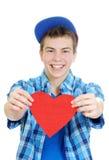 Adolescente sonriente que lleva a cabo el corazón de la tarjeta del día de San Valentín Fotos de archivo