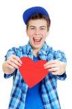 Adolescente sonriente que lleva a cabo el corazón de la tarjeta del día de San Valentín Foto de archivo libre de regalías