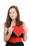 Adolescente sonriente que lleva a cabo el corazón de la tarjeta del día de San Valentín Fotos de archivo libres de regalías