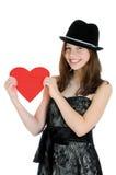 Adolescente sonriente que lleva a cabo el corazón de la tarjeta del día de San Valentín Imagen de archivo libre de regalías