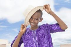Adolescente sonriente que lleva un sombrero de paja del navegante Foto de archivo