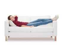 Adolescente sonriente que miente en el sofá Foto de archivo