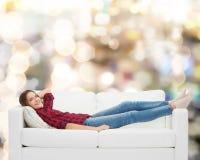 Adolescente sonriente que miente en el sofá Imagenes de archivo