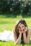 Adolescente sonriente que miente en hierba Fotografía de archivo