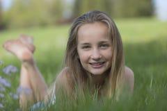Adolescente sonriente que miente en un prado de la primavera Fotografía de archivo