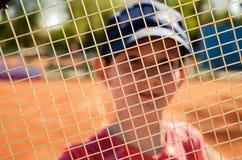 Adolescente sonriente que mira a través de la red de una estafa de tenis Foto de archivo libre de regalías