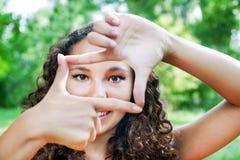 Adolescente sonriente que muestra el marco por las manos Fotografía de archivo libre de regalías