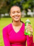 Adolescente sonriente que muestra la botella Fotografía de archivo libre de regalías