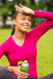 Adolescente sonriente que muestra la botella Fotografía de archivo