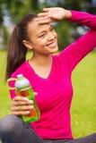Adolescente sonriente que muestra la botella Foto de archivo libre de regalías