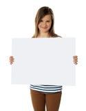 Adolescente sonriente que muestra la cartelera blanca en blanco Fotos de archivo libres de regalías
