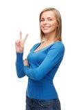 Adolescente sonriente que muestra la v-muestra con la mano Fotografía de archivo