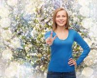 Adolescente sonriente que muestra la v-muestra con la mano Imagenes de archivo