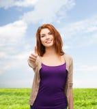 Adolescente sonriente que muestra los pulgares para arriba Foto de archivo libre de regalías