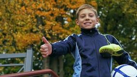 Adolescente sonriente que muestra los pulgares para arriba con un balón de fútbol en sus botas de la mano y del fútbol en el homb Fotos de archivo libres de regalías