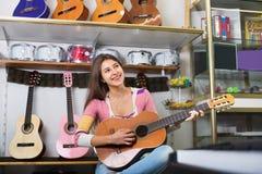Adolescente sonriente que presenta con la guitarra clásica Fotografía de archivo
