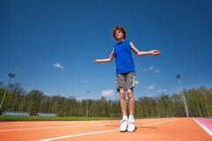Adolescente sonriente que salta la cuerda afuera Foto de archivo