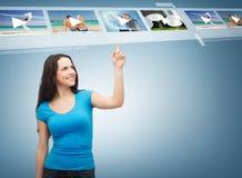Adolescente sonriente que señala sus vídeos del finger Fotos de archivo libres de regalías