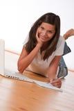 Adolescente sonriente que se acuesta con la computadora portátil Imagenes de archivo