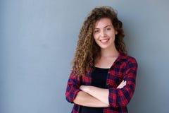Adolescente sonriente que se coloca con los brazos cruzados Fotos de archivo