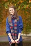 Adolescente sonriente que se coloca en parque del otoño Fotos de archivo