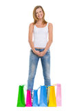 Adolescente sonriente que se coloca entre bolsos de compras Foto de archivo