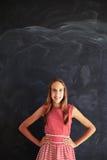 Adolescente sonriente que se opone con las manos en caderas a blackbo Foto de archivo libre de regalías