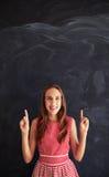 Adolescente sonriente que se opone a la pizarra y que muestra para Fotografía de archivo